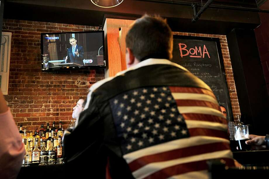 A man at the BoMA restaurant across the street from the Cathedral of the Holy Cross watches US President Barrack Obama on television speak at the cathedral where an interfaith prayer service to honor the victims of the Boston Marathon bombings was being held April 18, 2013 in the South End neighborhood of Boston, Massachusetts.  AFP PHOTO/Stan HONDASTAN HONDA/AFP/Getty Images Photo: Stan Honda, AFP/Getty Images