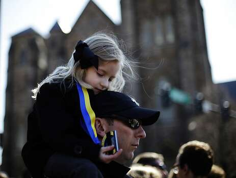 Marathon runner Nathan Finney of Boston and his daughter Mckenna, 5, gather with others ahead of an interfaith service with President Barack Obama at Cathedral of the Holy Cross, held in the wake of Monday's Boston Marathon explosions, which killed at least three and injured more than 140, Thursday, April 18, 2013, in Boston. (AP Photo/Matt Rourke) Photo: Matt Rourke, Associated Press