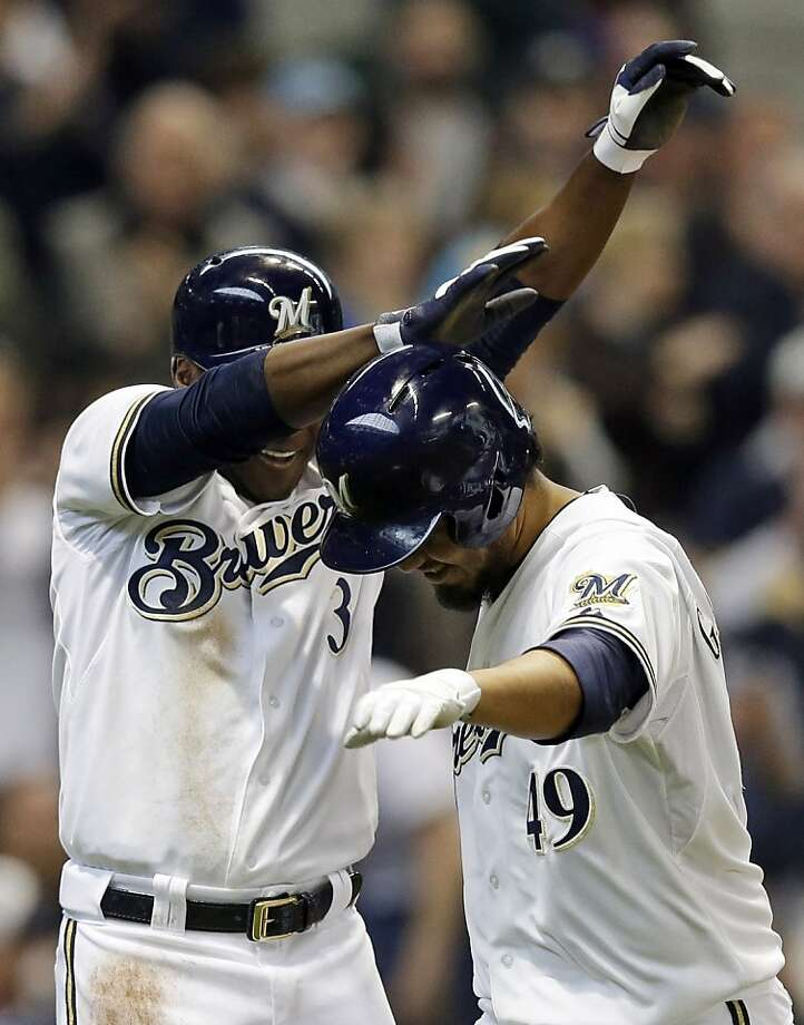 Milwaukee Brewers' Yovani Gallardo, right, is congratulated by teammate Yuniesky Betancourt after hitting a two-run home run during the second inning of a baseball game against the San Francisco Giants Thursday, April 18, 2013, in Milwaukee. (AP Photo/Morry Gash) Photo: Morry Gash, Associated Press