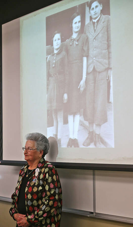 Behind Anna Rado  is a photo of herself, on the left, with her sister and brother. Unlike their parents, the siblings survived the Holocaust. Photo: Jerry Lara / San Antonio Express-News