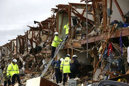 Firefighter conduct search and rescue of an apartment destroyed by an explosion at a fertilizer plant in West, Texas, Thursday, April 18, 2013.  A massive explosion at the West Fertilizer Co. killed as many as 15 people and injured more than 160, officials said overnight.  (AP Photo/LM Otero) Photo: LM Otero, Associated Press