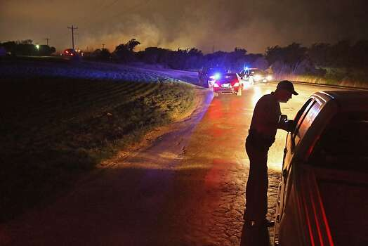 WEST, TX - APRIL 18:  With smoke rising in the distance, a law enformcement officer runs a check point at the perimeter about half a mile from the West Fertilizer Company April 18, 2013 in West, Texas. A massive explosion at the fertilizer company injured more than 100 people and left damaged buildings for blocks in every direction. The death toll from the blast, which occured as firefighters were tackling a blaze, is as yet unknown. (Photo by Chip Somodevilla/Getty Images) Photo: Chip Somodevilla, Getty Images