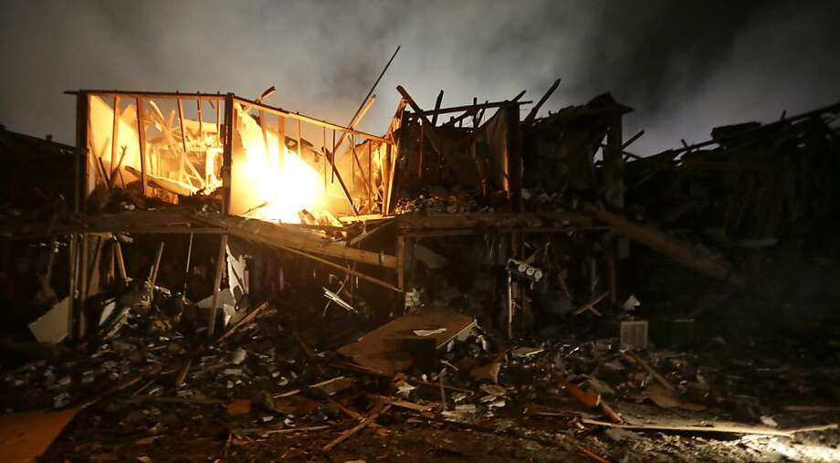 A fire burns in a apartment complex destroyed near a fertilizer plant that exploded earlier in West, Texas, in this photo made early Thursday morning, April 18, 2013.  (AP Photo/LM Otero) Photo: LM Otero, Associated Press