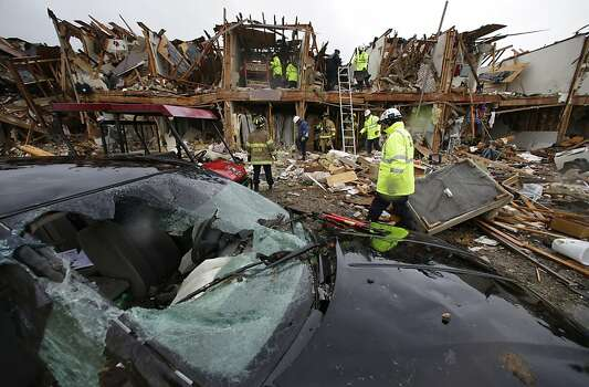 A destroyed car sits as firefighters conduct a search and rescue of an apartment complex destroyed by an explosion at a fertilizer plant in West, Texas, Thursday, April 18, 2013.  A massive explosion at the West Fertilizer Co. killed as many as 15 people and injured more than 160, officials said overnight.  (AP Photo/LM Otero) Photo: LM Otero, Associated Press