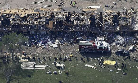 A Dallas Regional Urban Search and Rescue Truck sits parked by a destroyed apartment complex with emergency responders working the scene after it was destroyed by an explosion at a nearby fertilizer plant in West, Texas, Thursday, April 18, 2013. A massive explosion at the West Fertilizer Co. killed as many as 15 people and injured more than 160, officials said overnight. The explosion that struck around 8 p.m. Wednesday, sent flames shooting into the night sky and rained burning embers and debris down on shocked and frightened residents. (AP Photo/Tony Gutierrez) Photo: Tony Gutierrez, Associated Press