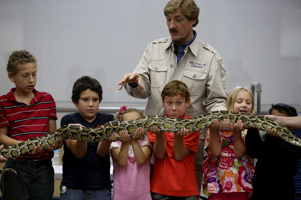 """Peter Gros, co-host of """"Mutual of Omaha's Wild Kingdom"""" television show, talks about the Burmese python as it's held by student volunteers including Antoine Arnosky (from left), Jacobo Ganon, Sarah Loftis, Henry Batchelder, Chloe Dixon and Jacob Guzman."""