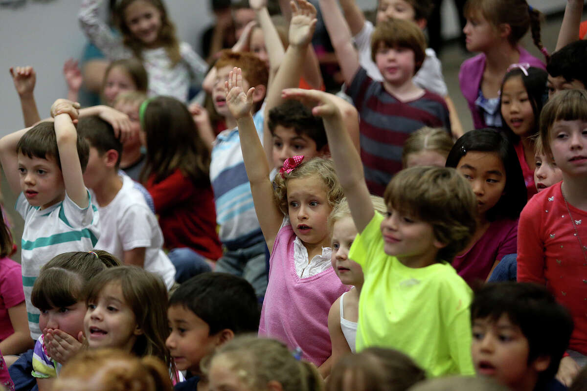 Students including Sarah Loftis, center, raise their hands in hopes of being chosen by naturalist Peter Gros, co-host of Mutual of Omaha's Wild Kingdom television show, to touch an animal, reptile or insect during his presentation at The Montessori School of San Antonio on Thursday, April 18, 2013.