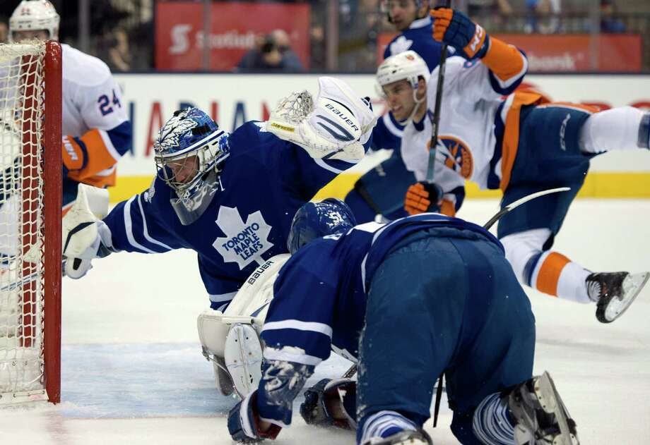 New York Islanders center John Tavares, right, flies through the air as his shot gets past Toronto Maple Leafs goaltender James Reimer and defenseman Jake Gardiner, foreground, during first-period NHL hockey game action in Toronto, Thursday, April 18, 2013. (AP Photo/The Canadian Press, Frank Gunn) Photo: Frank Gunn
