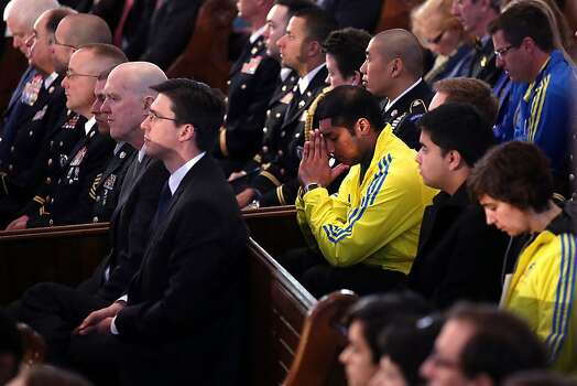 """BOSTON, MA - APRIL 18: Runners pray at an interfaith prayer service for victims of the Boston Marathon attack titled """"Healing Our City,"""" and attended by President Barack Obama and  first lady Michelle Obama at the Cathedral of the Holy Cross on April 18, 2013 in Boston, Massachusetts. Authorities investigating the attack on the Boston Marathon have shifted their focus to locating the person who placed a black bag down and walked away just before the bombs went off. The twin bombings at the 116-year-old Boston race, which occurred near the marathon finish line, resulted in the deaths of three people and more than 170 others injured.  (Photo by Spencer Platt/Getty Images) Photo: Spencer Platt, Getty Images"""