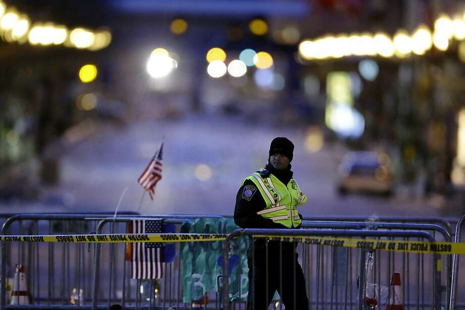 A police officer walks along a barricade on Boylston Street near the finish line of Monday's Boston Marathon explosions, which killed at least three and injured more than 140, Thursday, April 18, 2013, in Boston. (AP Photo/Matt Rourke) Photo: Matt Rourke, Associated Press