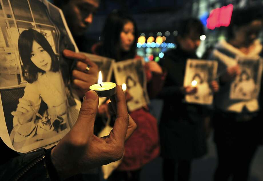 In this Wednesday, April 17, 2013 photo, Chinese hold pictures of Lu Lingzi, a Boston University graduate student from China who was killed Monday in the Boston Marathon explosions, as they hold candles to mourn for her in Shenyang in northeast China's Liaoning province. Lu was a graduate student studying mathematics and statistics and scheduled to receive her graduate degree in 2015. (AP Photo) CHINA OUT Photo: Associated Press