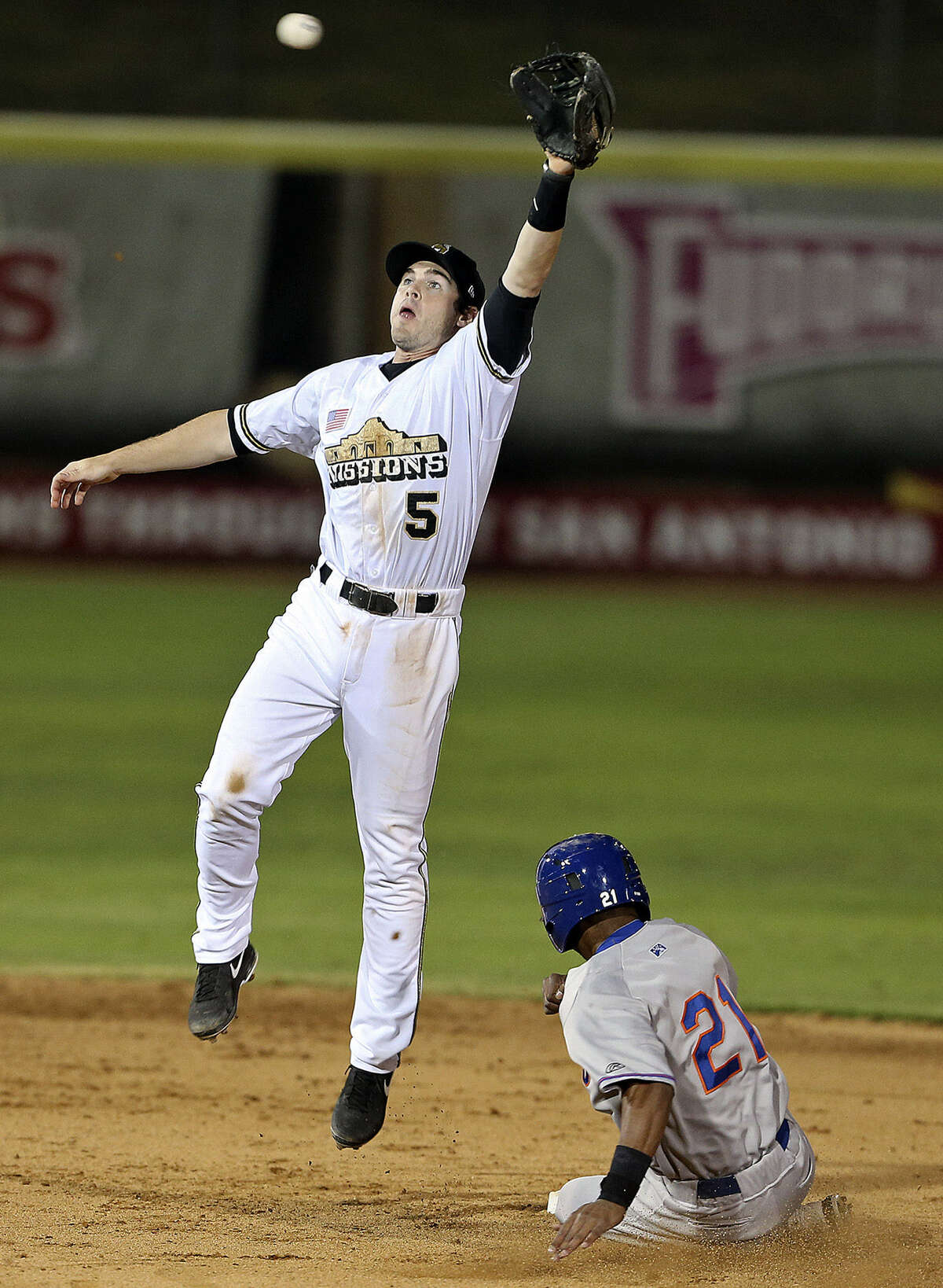 Missions shortstop Chris Bisson leaps to catch a high throw from the catcher as Midland's D'Arby Myers steals second base in the sixth inning.