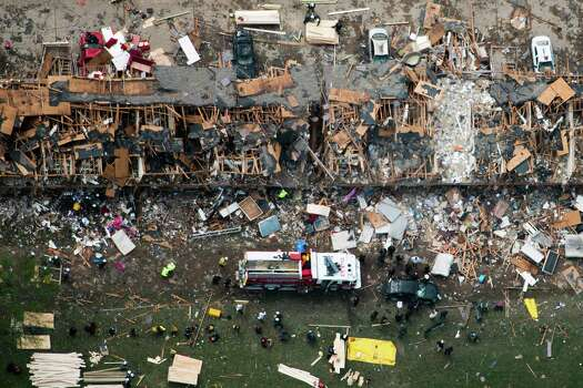 Law enforcement and rescue personnel search the damage to an apartment complex from the explosion of the West Fertilizer plant on Thursday, April 18, 2013, in West, Texas.  A massive explosion at the plant killed as many as 15 people and injured more than 160, officials said overnight.  ( Smiley N. Pool / Houston Chronicle ) Photo: Houston Chronicle / © 2013  Houston Chronicle