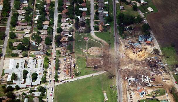 Damage from the explosion of the West Fertilizer plant, at right, is seen in an aerial view on Thursday, April 18, 2013, in West, Texas.  A nursing home is at left.  An apartment complex is at center. A massive explosion at the plant killed as many as 15 people and injured more than 160, officials said overnight.  ( Smiley N. Pool / Houston Chronicle ) Photo: Houston Chronicle / © 2013  Houston Chronicle