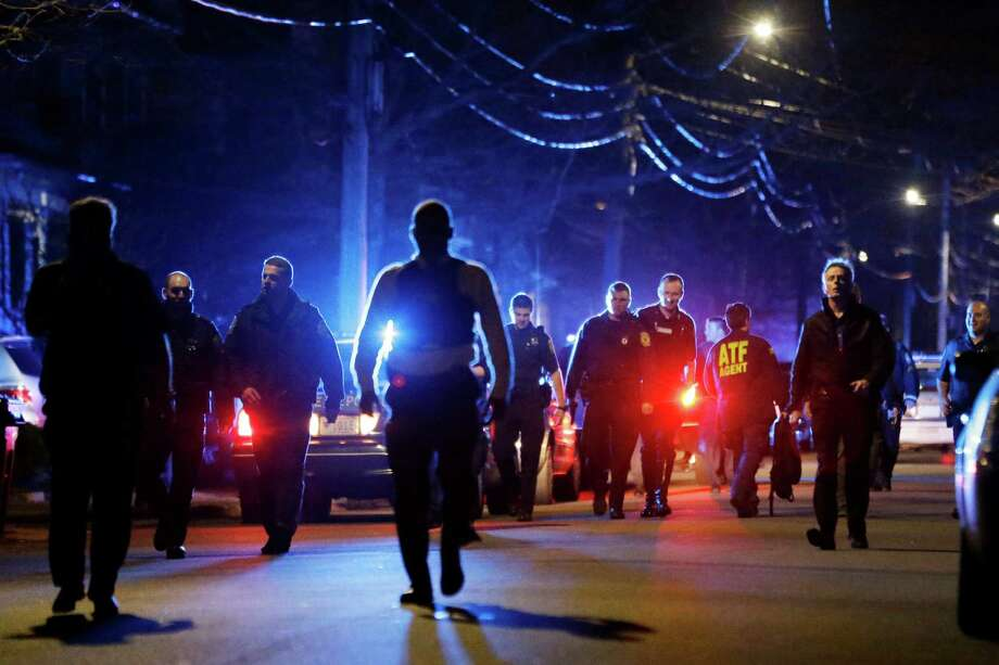 Police officers walk near a crime scene Friday, April 19, 2013, in Watertown, Mass. A tense night of police activity that left a university officer dead on campus just days after the Boston Marathon bombings and amid a hunt for two suspects caused officers to converge on a neighborhood outside Boston, where residents heard gunfire and explosions. Photo: AP