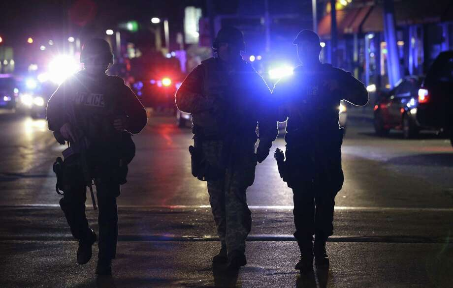 Officers wearing tactical gear arrive at the Watertown neighborhood of Boston, Friday, April 19, 2013. Reports of explosives being detonated and police are telling reporters to turn off their cell phones. Dozens of officers and National Guard members are in Watertown, where television outlets report that gunfire and explosions have been heard. (AP Photo/Julio Cortez) Photo: Julio Cortez, Associated Press / AP