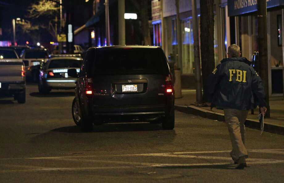 An FBI official arrives at the Watertown neighborhood of Boston, Friday, April 19, 2013. Reports of explosives being detonated and police are telling reporters to turn off their cell phones. Dozens of officers and National Guard members are in Watertown, where television outlets report that gunfire and explosions have been heard. (AP Photo/Julio Cortez) Photo: Julio Cortez, Associated Press / AP