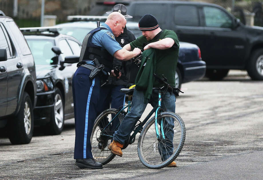 A Massachusetts State Police officer checks the bag of a cyclist during heightened security on April 19, 2013 in Watertown, Massachusetts. Earlier, a Massachusetts Institute of Technology campus police officer was shot and killed at the school's campus in Cambridge. A short time later, police reported exchanging gunfire with alleged carjackers in Watertown, a city near Cambridge. According to reports, one suspect has been killed during a car chase and the police are seeking another - believed to be the same person (known as Suspect Two) wanted in connection with the deadly bombing at the Boston Marathon earlier this week. Police have confirmed that the dead assailant is Suspect One from the recently released marathon bombing photographs. Photo: Mario Tama, Getty Images / 2013 Getty Images
