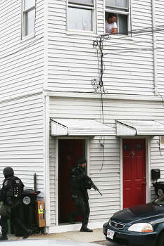 WATERTOWN, MA - APRIL 19:  SWAT team members search for one remaining suspect at a residential building as a man looks out from a window on April 19, 2013 in Watertown, Massachusetts. Earlier, a Massachusetts Institute of Technology campus police officer was shot and killed at the school's campus in Cambridge. A short time later, police reported exchanging gunfire with alleged carjackers in Watertown, a city near Cambridge. According to reports, one suspect has been killed during a car chase and the police are seeking another - believed to be the same person (known as Suspect Two) wanted in connection with the deadly bombing at the Boston Marathon earlier this week. Police have confirmed that the dead assailant is Suspect One from the recently released marathon bombing photographs. Photo: Mario Tama, Getty Images / 2013 Getty Images