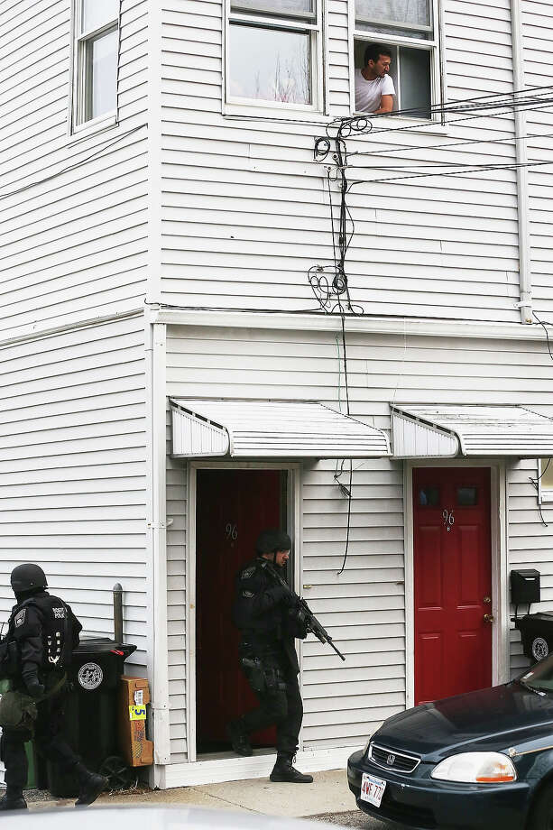 SWAT team members search for one remaining suspect at a residential building as a man looks out from a window on April 19, 2013 in Watertown, Massachusetts. Earlier, a Massachusetts Institute of Technology campus police officer was shot and killed at the school's campus in Cambridge. A short time later, police reported exchanging gunfire with alleged carjackers in Watertown, a city near Cambridge. According to reports, one suspect has been killed during a car chase and the police are seeking another - believed to be the same person (known as Suspect Two) wanted in connection with the deadly bombing at the Boston Marathon earlier this week. Police have confirmed that the dead assailant is Suspect One from the recently released marathon bombing photographs. Photo: Mario Tama, Getty Images / 2013 Getty Images