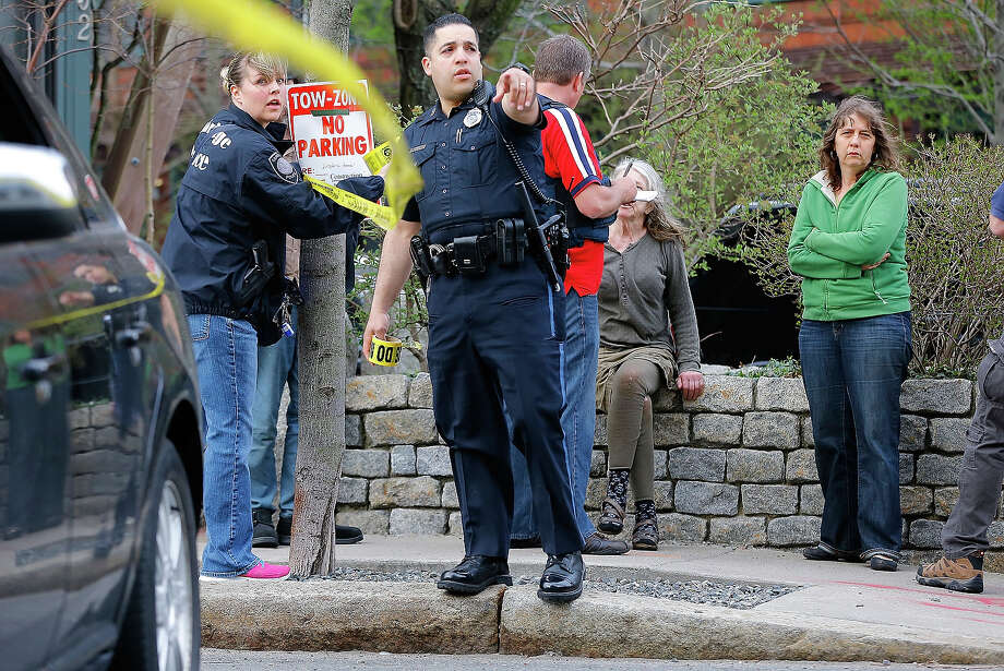 Members of the FBI, State Police, Boston Police, Cambridge Police, and other law enforcement agencies, put up police tape securing a perimeter in front of a woman being questioned by the FBI on April 19, 2013 near the home of suspect #2 on Norfolk Street in Cambridge, Massachusetts. Earlier, a Massachusetts Institute of Technology campus police officer was shot and killed late Thursday night at the school's campus in Cambridge. A short time later, police reported exchanging gunfire with alleged carjackers in Watertown, a city near Cambridge. According to reports, one suspect has been killed during a car chase and the police are seeking another - believed to be the same person (known as Suspect Two) wanted in connection with the deadly bombing at the Boston Marathon earlier this week. Police have confirmed that the dead assailant is Suspect One from the recently released marathon bombing photographs. Photo: Jared Wickerham, Getty Images / 2013 Getty Images