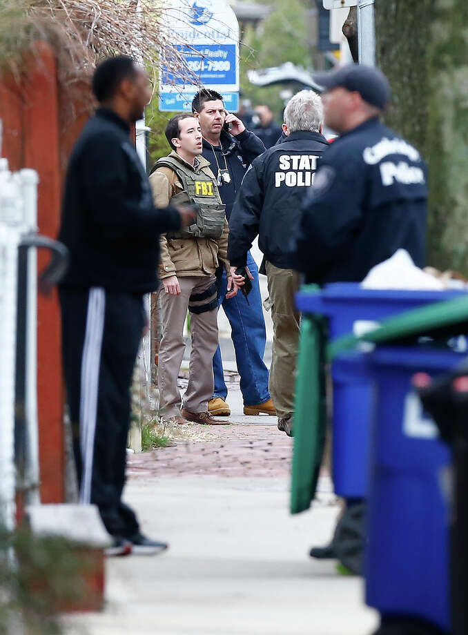 Members of the FBI, State Police, Boston Police, Cambridge Police, and other law enforcement agencies, survey the perimeter on April 19, 2013 near the home of suspect #2 on Norfolk Street in Cambridge, Massachusetts. Earlier, a Massachusetts Institute of Technology campus police officer was shot and killed late Thursday night at the school's campus in Cambridge. A short time later, police reported exchanging gunfire with alleged carjackers in Watertown, a city near Cambridge. According to reports, one suspect has been killed during a car chase and the police are seeking another - believed to be the same person (known as Suspect Two) wanted in connection with the deadly bombing at the Boston Marathon earlier this week. Police have confirmed that the dead assailant is Suspect One from the recently released marathon bombing photographs. Photo: Jared Wickerham, Getty Images / 2013 Getty Images