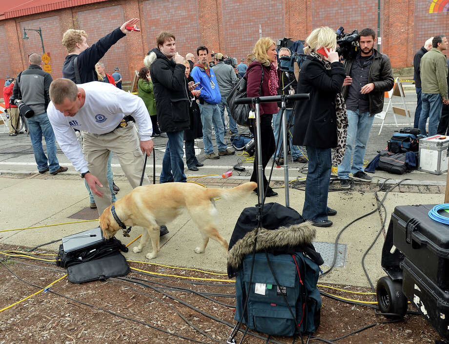 A dog sniffs equipment before Massachusetts Governor Deval Patrick spoke to the media at a shopping mall on the perimeter of a locked down area as a search for the second of two suspects wanted in the Boston Marathon bombings takes place on April 19, 2013 in Watertown, Massachusetts. AFP PHOTO/Stan HONDA Photo: STAN HONDA, Getty Images / 2013 AFP