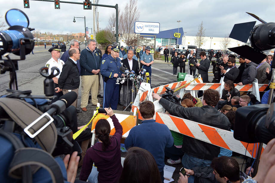 Colonel Timothy Albens (C, at microphone), Massachusetts State Police, with Massachusetts Governor Deval Patrick (R) and Boston Police Commissioner Ed Davis (L) speaks to the media at a shopping mall on the perimeter of a locked down area as a search for the second of two suspects wanted in the Boston Marathon bombings takes place April 19, 2013 in Watertown, Massachusetts. AFP PHOTO/Stan HONDA Photo: STAN HONDA, Getty Images / 2013 AFP