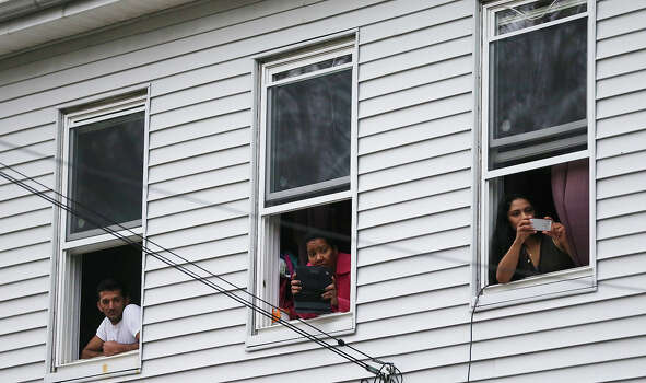 WATERTOWN, MA - APRIL 19:  Onlookers take pictures as they watch from windows while SWAT team members search for one remaining suspect at a neighboring apartment building on April 19, 2013 in Watertown, Massachusetts. Earlier, a Massachusetts Institute of Technology campus police officer was shot and killed at the school's campus in Cambridge. A short time later, police reported exchanging gunfire with alleged carjackers in Watertown, a city near Cambridge. According to reports, one suspect has been killed during a car chase and the police are seeking another - believed to be the same person (known as Suspect Two) wanted in connection with the deadly bombing at the Boston Marathon earlier this week. Police have confirmed that the dead assailant is Suspect One from the recently released marathon bombing photographs. Photo: Mario Tama, Getty Images / 2013 Getty Images