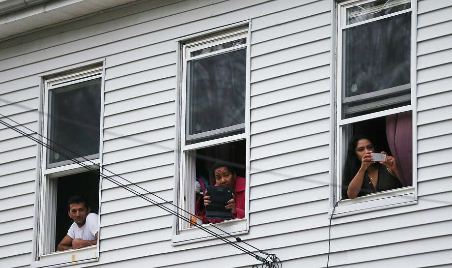 Onlookers take pictures as they watch from windows while SWAT team members search for one remaining suspect at a neighboring apartment building on April 19, 2013 in Watertown, Massachusetts. Earlier, a Massachusetts Institute of Technology campus police officer was shot and killed at the school's campus in Cambridge. A short time later, police reported exchanging gunfire with alleged carjackers in Watertown, a city near Cambridge. According to reports, one suspect has been killed during a car chase and the police are seeking another - believed to be the same person (known as Suspect Two) wanted in connection with the deadly bombing at the Boston Marathon earlier this week. Police have confirmed that the dead assailant is Suspect One from the recently released marathon bombing photographs. Photo: Mario Tama, Getty Images / 2013 Getty Images