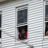 WATERTOWN, MA - APRIL 19:  Onlookers take pictures as they watch from windows while SWAT team members search for one remaining suspect at a neighboring apartment building on April 19, 2013 in Watertown, Massachusetts. Earlier, a Massachusetts Institute of Technology campus police officer was shot and killed at the school's campus in Cambridge. A short time later, police reported exchanging gunfire with alleged carjackers in Watertown, a city near Cambridge. According to reports, one suspect has been killed during a car chase and the police are seeking another - believed to be the same person (known as Suspect Two) wanted in connection with the deadly bombing at the Boston Marathon earlier this week. Police have confirmed that the dead assailant is Suspect One from the recently released marathon bombing photographs.