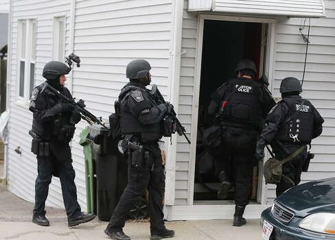 WATERTOWN, MA - APRIL 19:  SWAT team members search for one remaining suspect at a residential building on April 19, 2013 in Watertown, Massachusetts. Earlier, a Massachusetts Institute of Technology campus police officer was shot and killed at the school's campus in Cambridge. A short time later, police reported exchanging gunfire with alleged carjackers in Watertown, a city near Cambridge. According to reports, one suspect has been killed during a car chase and the police are seeking another - believed to be the same person (known as Suspect Two) wanted in connection with the deadly bombing at the Boston Marathon earlier this week. Police have confirmed that the dead assailant is Suspect One from the recently released marathon bombing photographs. Photo: Mario Tama, Getty Images / 2013 Getty Images