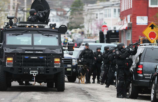 WATERTOWN, MA - APRIL 19:  SWAT team members aim their guns as they search for one remaining suspect at an apartment building on April 19, 2013 in Watertown, Massachusetts. Earlier, a Massachusetts Institute of Technology campus police officer was shot and killed at the school's campus in Cambridge. A short time later, police reported exchanging gunfire with alleged carjackers in Watertown, a city near Cambridge. According to reports, one suspect has been killed during a car chase and the police are seeking another - believed to be the same person (known as Suspect Two) wanted in connection with the deadly bombing at the Boston Marathon earlier this week. Police have confirmed that the dead assailant is Suspect One from the recently released marathon bombing photographs. Photo: Mario Tama, Getty Images / 2013 Getty Images