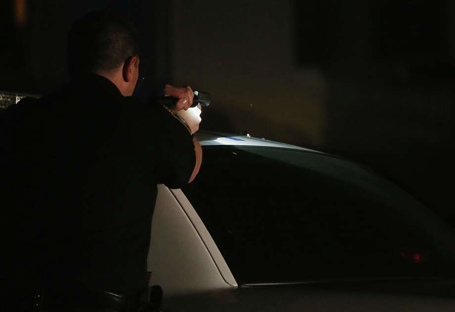 A police officer with gun drawn and flashlight searches for a suspect on April 19, 2013 in Watertown, Massachusetts. Earlier, a Massachusetts Institute of Technology campus police officer was shot and killed late Thursday night at the school's campus in Cambridge. A short time later, police reported exchanging gunfire with alleged carjackers in Watertown, a city near Cambridge. According to reports, one suspect has been killed during a car chase and the police are seeking another - believed to be the same person (known as Suspect Two) wanted in connection with the deadly bombing at the Boston Marathon earlier this week. Police have confirmed that the dead assailant is Suspect One from the recently released marathon bombing photographs. Photo: Mario Tama, Getty Images / 2013 Getty Images