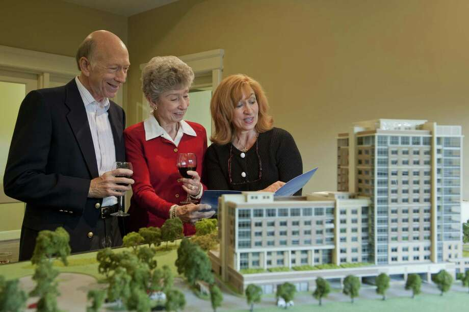 Carl Williams, Dorothy Anderson and Donna Giorgio view the model of the new tower expansion opening in 2015.