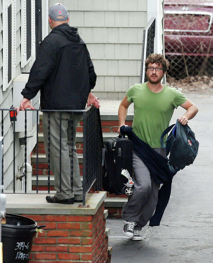 A resident evacuates as police go door-to-door on Norfolk Street in search of a suspect in the Boston Marathon bombings in Cambridge, Mass., Friday, April 19, 2013. Two suspects in the Boston Marathon bombing killed an MIT police officer, injured a transit officer in a firefight and threw explosive devices at police during a getaway attempt in a long night of violence that left one of them dead and another still at large Friday, authorities said as the manhunt intensified for a young man described as a dangerous terrorist. Photo: Michael Dwyer, Getty Images / AP2013