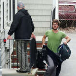 A resident evacuates as police go door-to-door on Norfolk Street in search of a suspect in the Boston Marathon bombings in Cambridge, Mass., Friday, April 19, 2013. Two suspects in the Boston Marathon bombing killed an MIT police officer, injured a transit officer in a firefight and threw explosive devices at police during a getaway attempt in a long night of violence that left one of them dead and another still at large Friday, authorities said as the manhunt intensified for a young man described as a dangerous terrorist.
