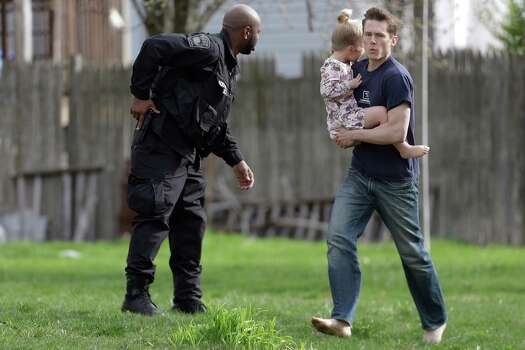 A police officer evacuates a shoeless man holding a child as members of law enforcement conduct a search for a suspect in the Boston Marathon bombings, Friday, April 19, 2013, in Watertown, Mass.  The two suspects in the Boston Marathon bombing killed an MIT police officer and hurled explosives at police in a car chase and gun battle overnight that left one of them dead and his brother on the loose, authorities said Friday as thousands of officers swarmed the streets in a manhunt that all but paralyzed the Boston area. Photo: Associated Press