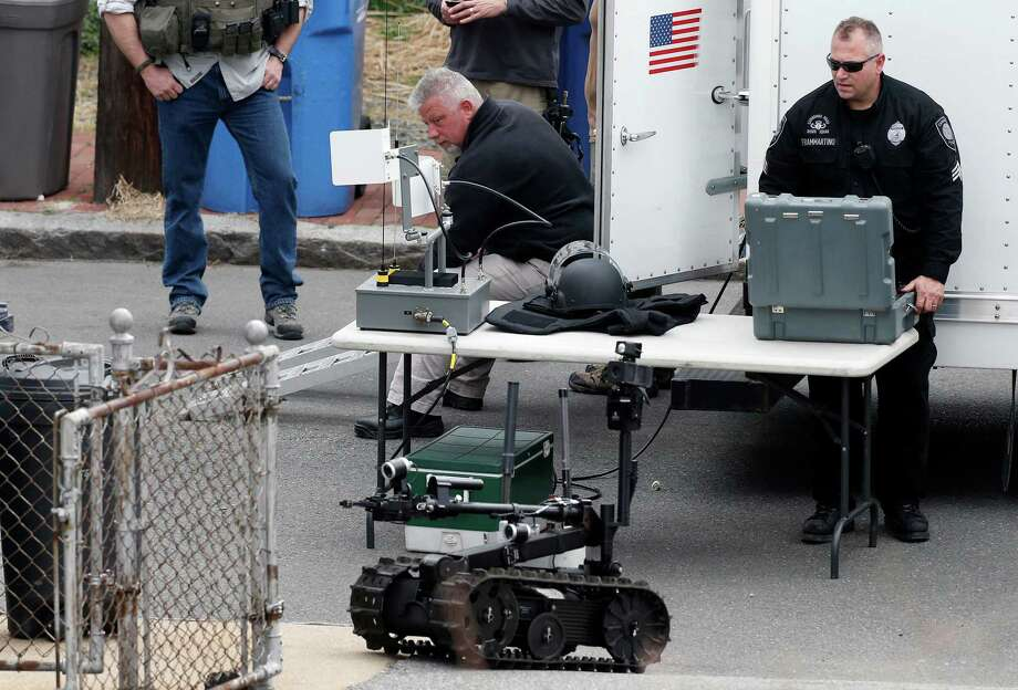A member of the Cambridge police bomb squad, right, deploys a robot on Norfolk Street during a search for searching a suspect in the Boston Marathon bombings in Cambridge, Mass., Friday, April 19, 2013. Two suspects in the Boston Marathon bombing killed an MIT police officer, injured a transit officer in a firefight and threw explosive devices at police during a getaway attempt in a long night of violence that left one of them dead and another still at large Friday, authorities said as the manhunt intensified for a young man described as a dangerous terrorist. Photo: Associated Press