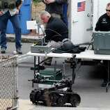 A member of the Cambridge police bomb squad, right, deploys a robot on Norfolk Street during a search for searching a suspect in the Boston Marathon bombings in Cambridge, Mass., Friday, April 19, 2013. Two suspects in the Boston Marathon bombing killed an MIT police officer, injured a transit officer in a firefight and threw explosive devices at police during a getaway attempt in a long night of violence that left one of them dead and another still at large Friday, authorities said as the manhunt intensified for a young man described as a dangerous terrorist.
