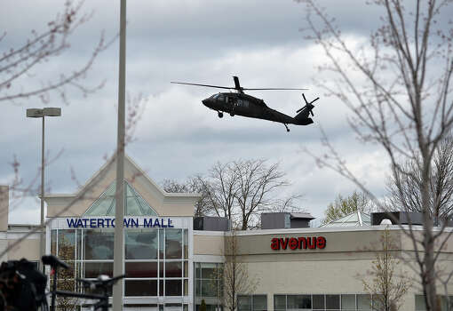 A National Guard helicopter prepares to land behind the Watertown Mall as a search for the second of two suspects wanted in the Boston Marathon bombings takes place April 19, 2013 in Watertown, Massachusetts. Thousands of heavily armed police staged an intense manhunt Friday for a Chechen teenager suspected in the Boston marathon bombings with his brother, who was killed in a shootout. Dzhokhar Tsarnaev, 19, defied the massive force after his 26-year-old brother Tamerlan was shot and suffered critical injuries from explosives believed to have been strapped to his body.     AFP PHOTO/Stan HONDA Photo: STAN HONDA, Getty Images / 2013 AFP