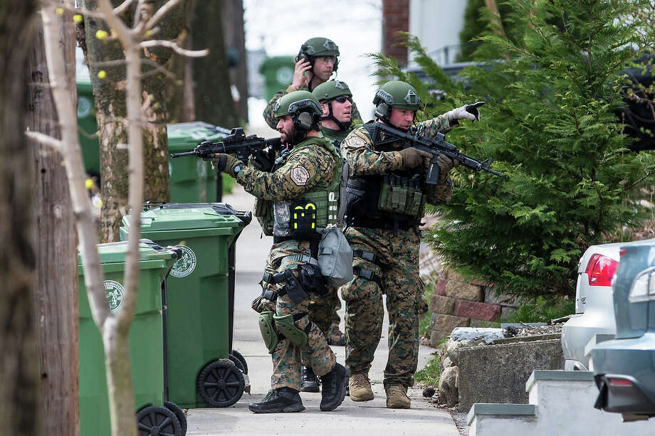 SWAT teams searched homes along Winsor Avenue in Watertown while searching for one of the two suspects in the terrorist bombing of the 117th Boston Marathon earlier this week. Photo: Boston Globe, Getty Images / 2013 - The Boston Globe