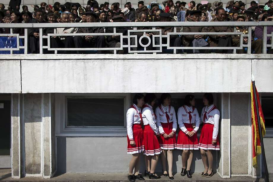 North Korean military veterans, above, and young women, right, attend a ceremony of the Korean Children's Union at a Pyongyang stadium April 12. Photo: Alexander F. Yuan, Associated Press