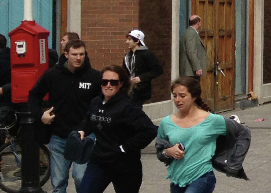 This Monday, April 15, 2013, shows a man who was dubbed Suspect No. 2 in the Boston Marathon bombings by law enforcement, in the upper center of the frame, wearing a white baseball cap, walking away from the scene of the explosions. The FBI identified him as 19-year-old college student Dzhokhar Tsarnaev, who along with his brother Tamerlan, 26, previously known as Suspect No. 1, killed an MIT police officer, severely wounded another lawman and hurled explosives at police in a car chase and gun battle during a night of violence, early Friday, April 19, 2013. Tamerlan Tsarnaev was killed overnight, officials said, while his brother Dzhokhar remains at large. Photo: Associated Press