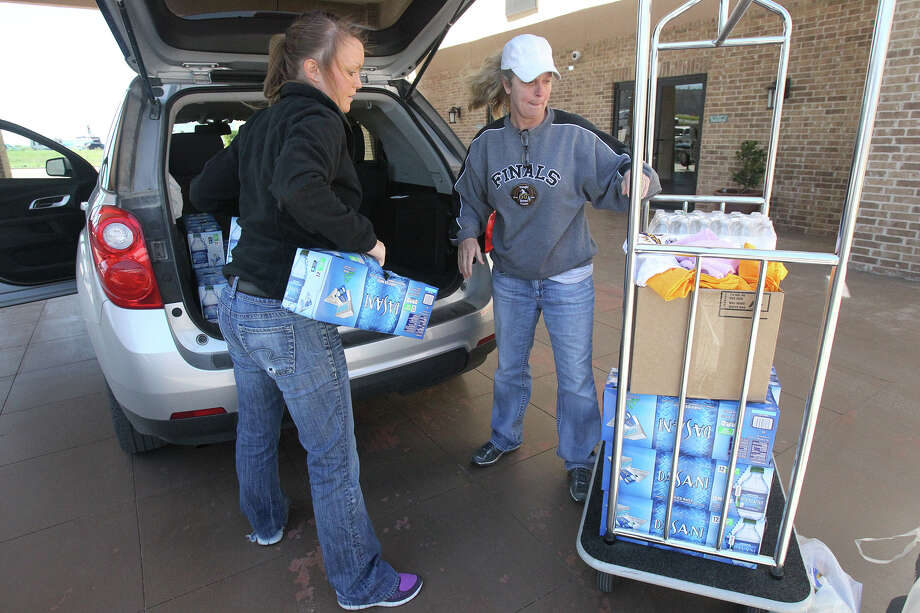 Volunteers Mallory Ferrier (left) and Christy Kolacek unload water Friday April 19, 2013 at the Best Western Hotel in West, Texas. Ferrier and Kolacek were unloading free provisions for people affected by the fertilizer plant explosion in West Wednesday night. Photo: JOHN DAVENPORT, SAN ANTONIO EXPRESS-NEWS / SAN ANTONIO EXPRESS-NEWS