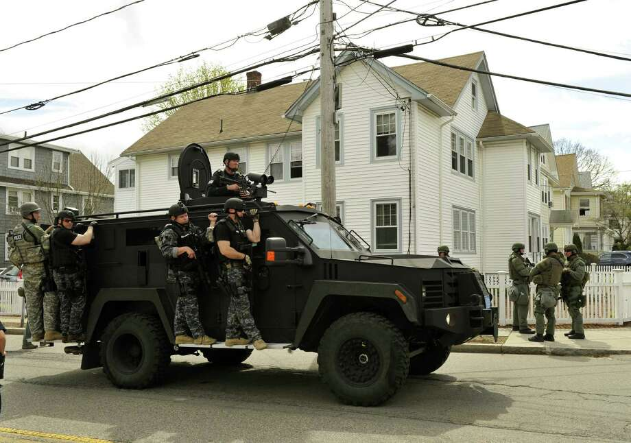 A police SWAT team search houses for the second of two suspects wanted in the Boston Marathon bombings takes place April 19, 2013 in Watertown, Massachusetts. Thousands of heavily armed police staged an intense manhunt Friday for a Chechen teenager suspected in the Boston marathon bombings with his brother, who was killed in a shootout. Dzhokhar Tsarnaev, 19, defied the massive force after his 26-year-old brother Tamerlan was shot and suffered critical injuries from explosives believed to have been strapped to his body.      AFP PHOTO / TIMOTHY A. CLARY Photo: Getty Images