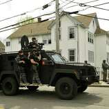A police SWAT team search houses for the second of two suspects wanted in the Boston Marathon bombings takes place April 19, 2013 in Watertown, Massachusetts. Thousands of heavily armed police staged an intense manhunt Friday for a Chechen teenager suspected in the Boston marathon bombings with his brother, who was killed in a shootout. Dzhokhar Tsarnaev, 19, defied the massive force after his 26-year-old brother Tamerlan was shot and suffered critical injuries from explosives believed to have been strapped to his body.      AFP PHOTO / TIMOTHY A. CLARY