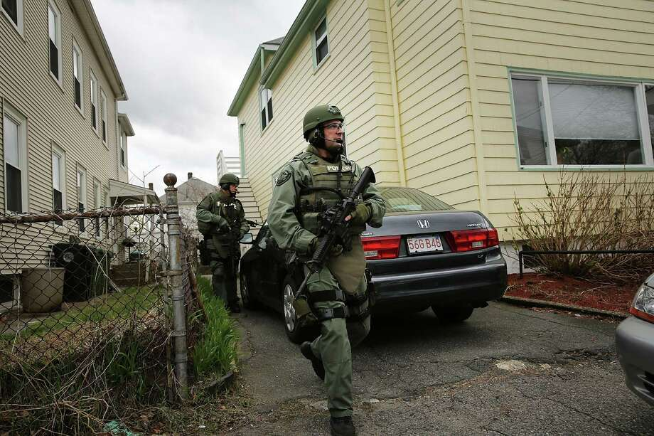 Members of a police SWAT team conduct a door-to-door search for 19-year-old Boston Marathon bombing suspect Dzhokhar A. Tsarnaev on April 19, 2013 in Watertown, Massachusetts. After a car chase and shoot out with police, one suspect in the Boston Marathon bombing, Tamerlan Tsarnaev, 26, was shot and killed by police early morning April 19, and a manhunt is underway for his brother and second suspect, 19-year-old Dzhokhar A. Tsarnaev. The two men are suspects in the bombings at the Boston Marathon on April 15, that killed three people and wounded at least 170. Photo: Spencer Platt, Getty Images / 2013 Getty Images