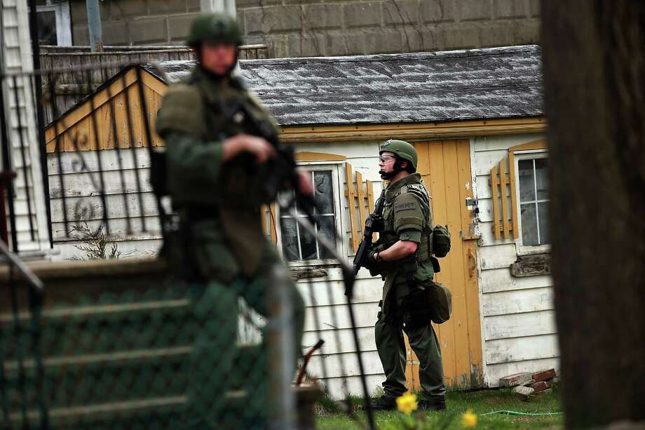 Members of a police S.W.A.T. team search through a neighborhood in Watertown as they search for 19-year-old bombing suspect Dzhokhar A. Tsarnaev on April 19, 2013 in Watertown, Massachusetts. After a car chase and shoot out with police, one suspect in the Boston Marathon bombing, Tamerlan Tsarnaev, 26, was shot and killed by police early morning April 19, and a manhunt is underway for his brother and second suspect, 19-year-old Dzhokhar A. Tsarnaev. The two men are suspects in the bombings at the Boston Marathon on April 15, that killed three people and wounded at least 170. Photo: Spencer Platt, Getty Images / 2013 Getty Images