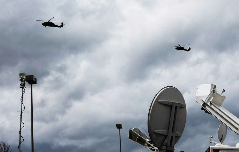 U.S. military helicopters fly over mobile television dishes during the search for 19-year-old Boston Marathon bombing suspect Dzhokhar A. Tsarnaev on April 19, 2013 in Watertown, Massachusetts. After a car chase and shoot out with police, one suspect in the Boston Marathon bombing, Tamerlan Tsarnaev, 26, was shot and killed by police early morning April 19, and a manhunt is underway for his brother and second suspect, 19-year-old Dzhokhar A. Tsarnaev. The two men are suspects in the bombings at the Boston Marathon on April 15, that killed three people and wounded at least 170. Photo: Mario Tama, Getty Images / 2013 Getty Images